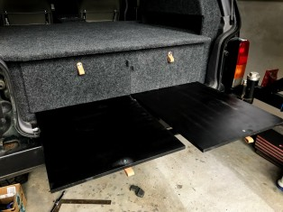 Under the drawers, we have the extension board we use to sleep. Also doubles as a cooking surface since Norma's trunk provides a natural cover. It's sprayed with truck bedding which makes it waterproof!